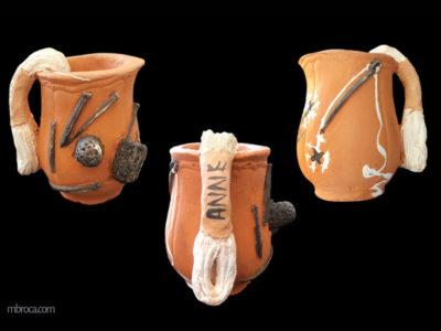 un bol vu sous trois faces différentes. L'anse est un écheveau de fil blanc, des aiguilles, un dé et une bobine sont collés au bol. des dessins de points de croix.