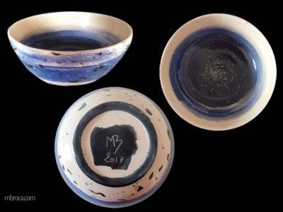 Trois vues d'une coupe, dessus, dessous et de côté. Décors abstrait bleu et noir sur fond crème, faisant penser à des oiseaux sur la mer.