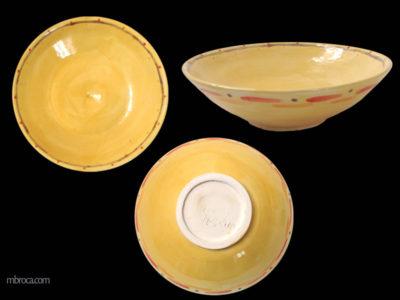 Trois vues d'une coupe jaune avec des décorations oranges, rouges et violettes.