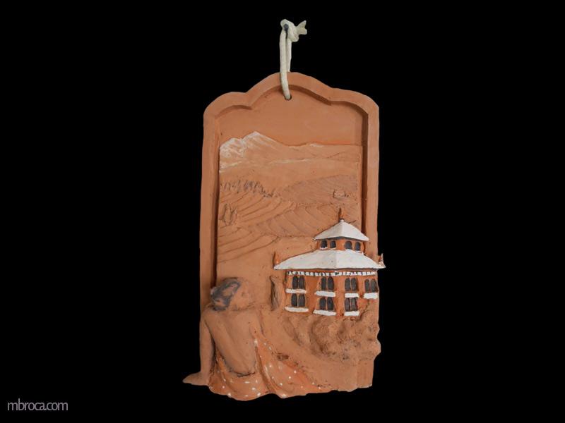 Bas relief en céramique une femme à gauche de dos. Elle a le dos nu et un tissus lui cache la poitrine et les jambes. À droite un temple, au fond des montagnes.