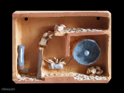 une étagère en céramique en position horizontale. Il y a des cases qui communiquent entre elles. Un biberon, une roue et une mangeaoire en terre sont fixées aux paroies. Trois cobayes jouent dans cette cage.