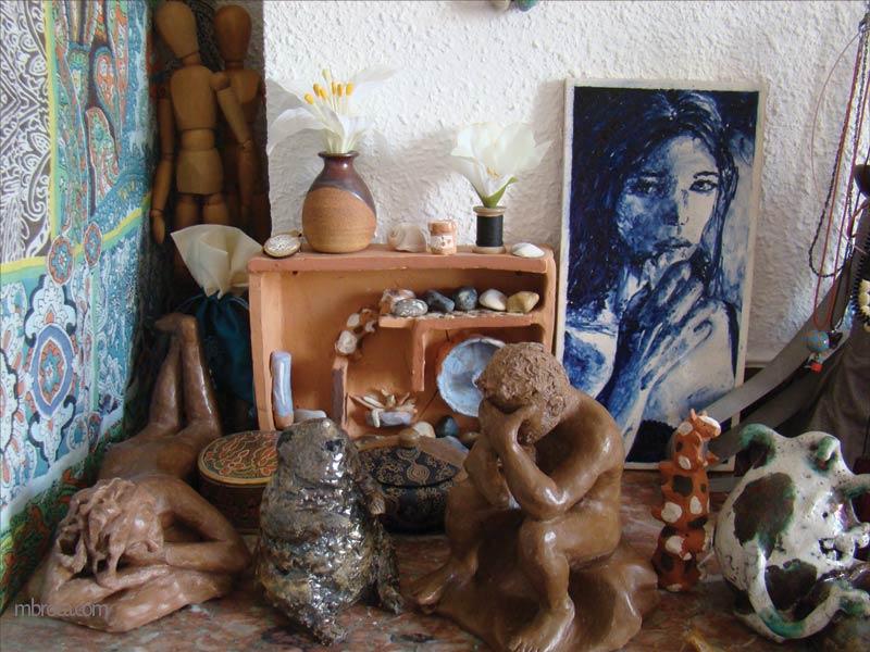 Page pour contacter. Différentes céramiques posées sur un rebord de cheminée. Deux manequins en bois, une femme alongée en terre, une marmotte et un monstre en raku, un homme pensant en argile, une étagère avec des cobayes, un azuleros représentant une femme. Divers objets comme des boites et des cailloux.