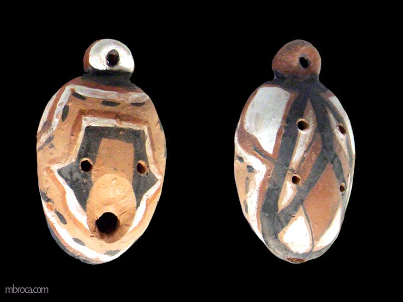 un ocarina ovale vu des deux faces. Il a des motifs géométriques de desiné.