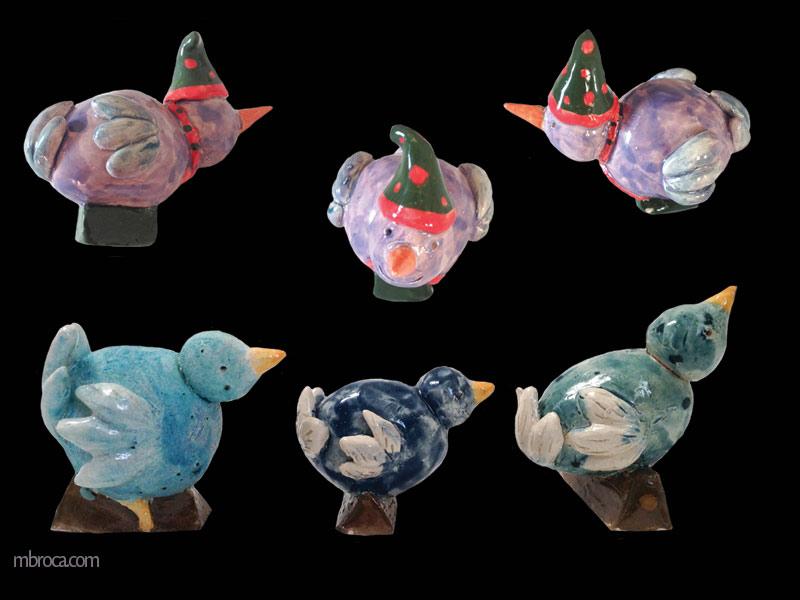 Quatre oiseaux. Trois bleus et un violet avec bonnet et écharpe vu sous trois positions.