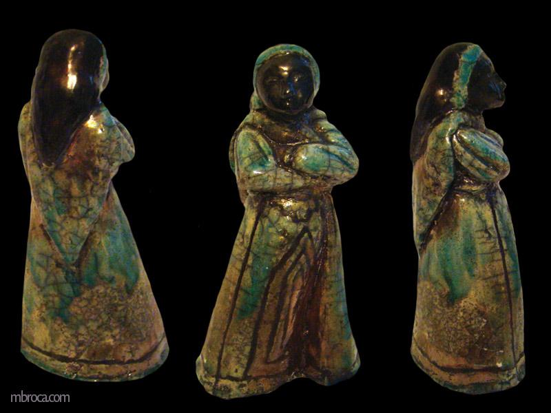 une femme le visage noir, un foulard sur la tête, une robe verte avec des motifs.