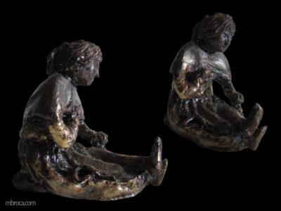 Une femme assise en train d'enfiler des perles.