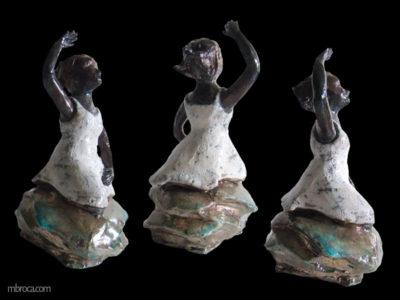 Une jeune fille avec une robe blance, un bras levé. Elle a les jambes qui disparraissent dans une vague.