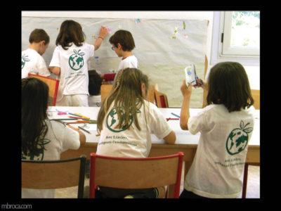 des enfants réalisent une fresque. Certains dessinent, d'autrent découpent et d'autres collent sur un grand papier
