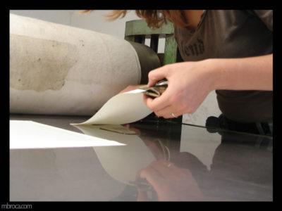 une personne en train de poser une feuille sur sa matrice pour imprimer.