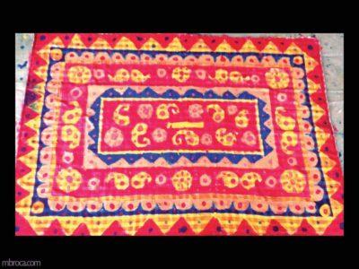 un tapis rouge avec des motifs jaunes et bleus.