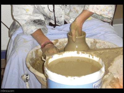 une personne en train de fabriquer un pot en terre à l'aide d'un tour