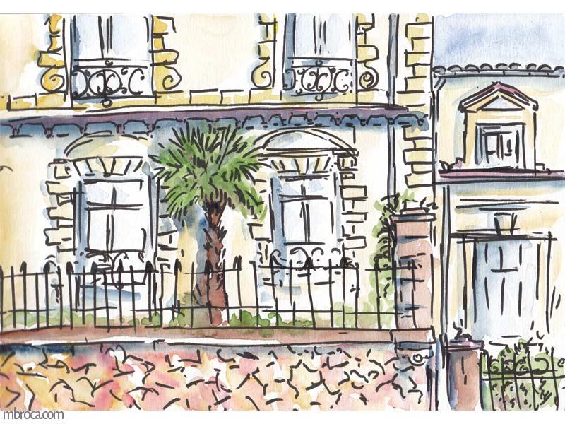 un immeuble bourgeois de narbonne, grille en fer mur en pierre. palmier.
