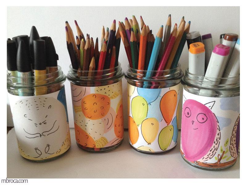 quatre pots avec des crayons et des étiquettes décorées.