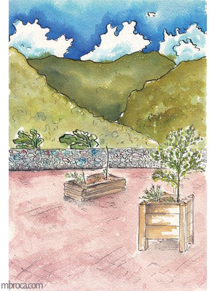 vue de la place de la mairie de mosset. Des bacs avec plantations, un muret et des montagnes en arrière plan.