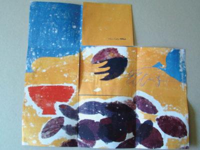 Le livre presque entièrement déplié, la silhouette d'un enfant qui mange une prune. Au premier plan des prunes et un bol.