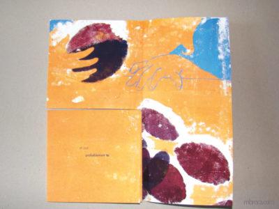 """Sept poèmes, une partie du livre déplié. """"et que probablement tu"""" deux mains et une prune qui a des traces de dents"""