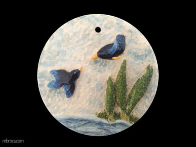 Céramique, un bas relief circulaire. Deux oiseaux dans le ciel se rejoignent, cependant que trois arbres ondulent au bord de l'eau.