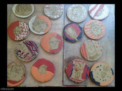 Projet pédagogique. Des plaques rondes. Sont gravées dessus des dessins de masques africains.