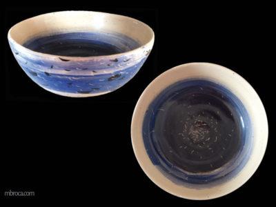 Décors abstrait bleu et noir sur fond crème, faisant penser à des oiseaux sur la mer.