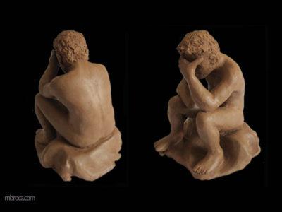 un homme assis, la tête dans une main. L'autre bras se termine par un moignon.