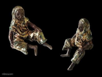 une femme avec un voile qui rejoint sa robe, pieds nus. Elle est assise une main sur son genoux.