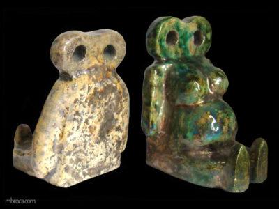 Deux personnages assis et stylisés. La tête est un huit alongé avec deux trous pour les yeux. leurs dos sont plats pour pouvoir maintenir les livres. L'homme a une dominante coloré ocre et la femme verte.