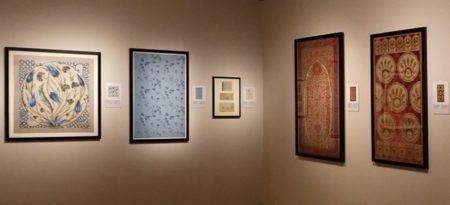 une salle d'exposition avec 5 cadres et des tissus imprimés.