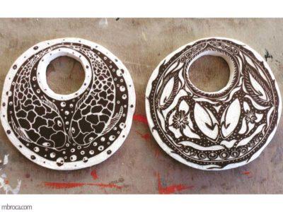 Oeuvre de 2018, deux céramiques rondes noires et blanches. Deux carpes sur l'une et des formes abstraites sur l'autre
