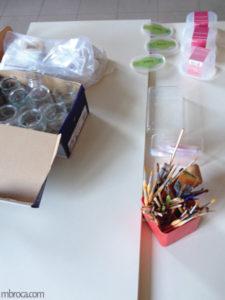 Des pots en verre, des boites en plastique, et des pinceaux